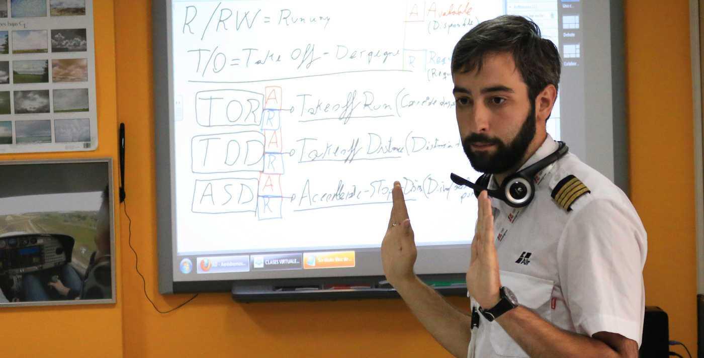 instructor de pilotos de avión enseñando en aula con pizarra digital