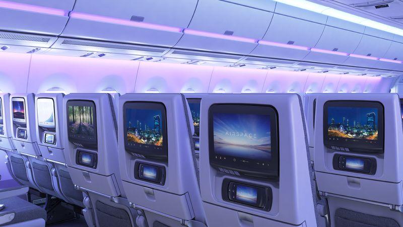 detalle de asientos de avion de pasajeros desde atras con pantallas iluminadas y luces violeeta