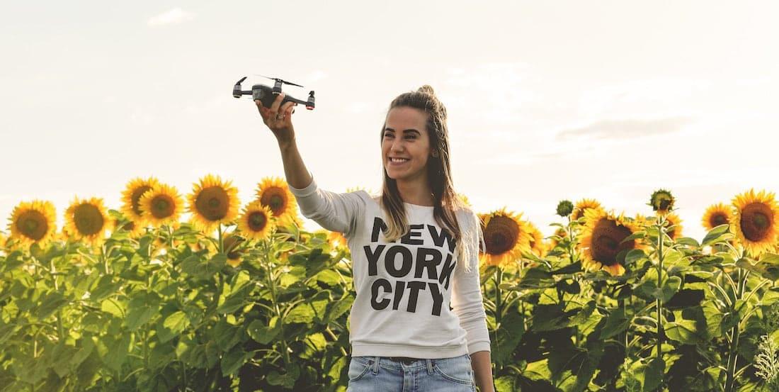 mujer joven con sudadera de nyc sujetando un dron con fondo de campo de girasoles y luz dorada de atardecer