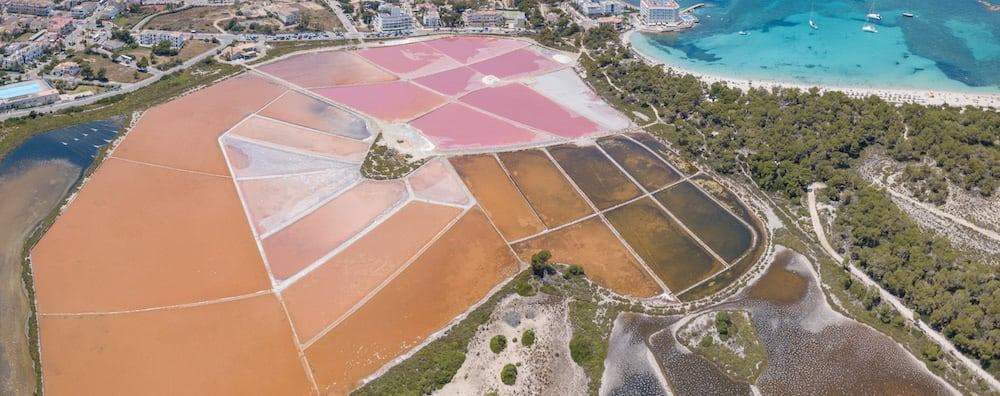 vista aerea de salinas de color rosado con mar turquesa al fondo