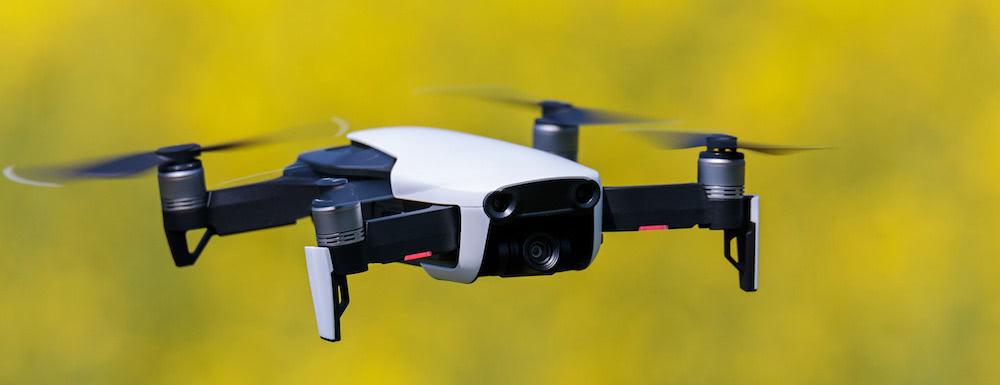 pequeno dron en vuelo sobre fondo amarillo difuminado
