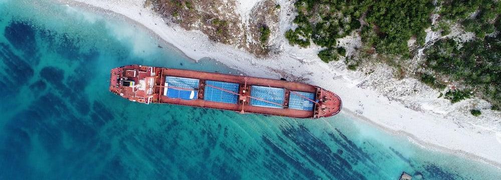 vista aerea de barco encallado en playa de arena blanca con vegetacion y agua turquesa