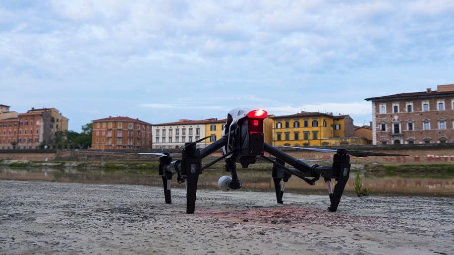 dron dji inspire posado en el suelo con edificios al fondo y cielo nublado
