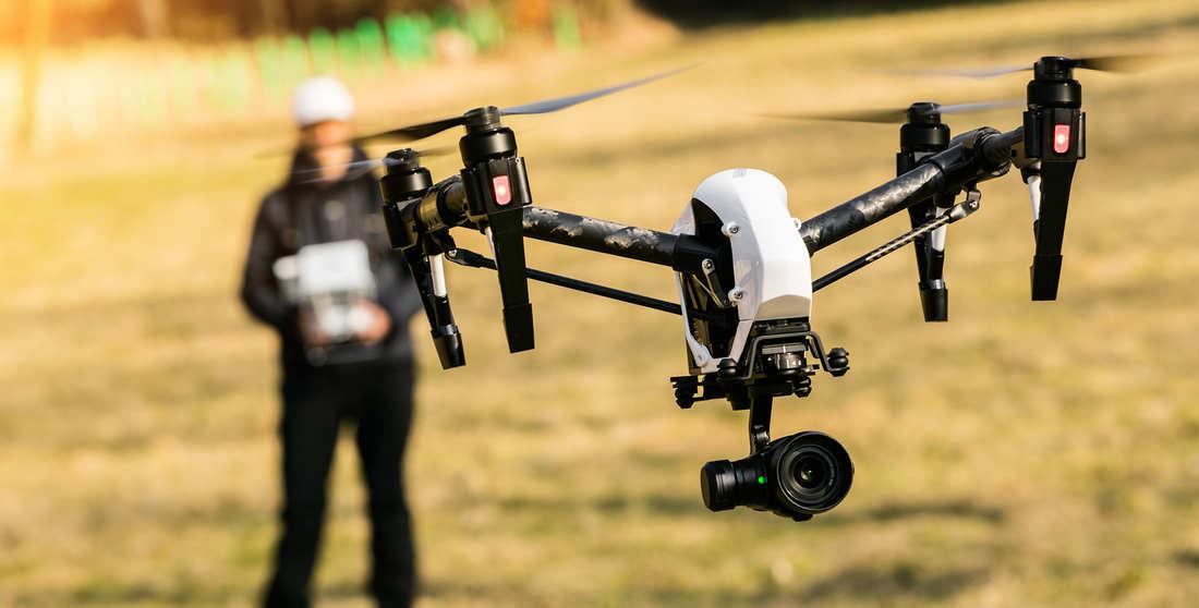 dron dji inspire color blanco en vuelo, piloto de drones detras con fondo de campo difuminado