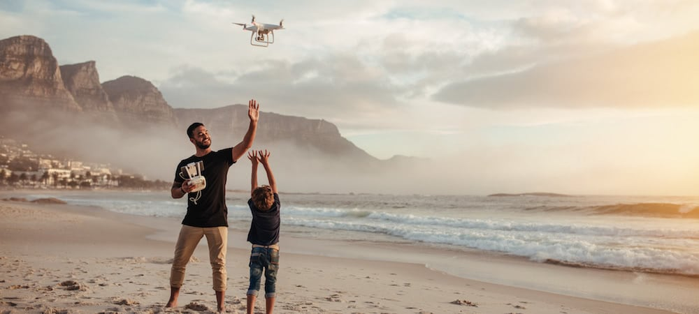 hombre y niño volando dron en playa con niebla y luz dorada