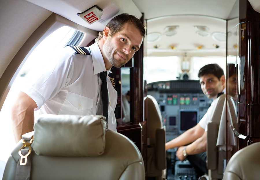 dos pilotos comerciales en cabina de avion mirando hacia la parte de atras del avion
