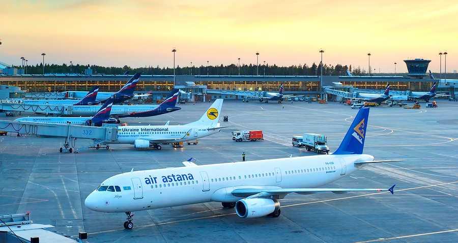 avion de la aerolina air astana parado en el aeropuerto y a su lado 5 aviones mas de otras aerolineas