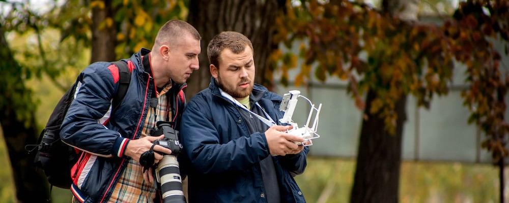 piloto de dron con emisora mostrando imagenes a fotografo con camara profesional