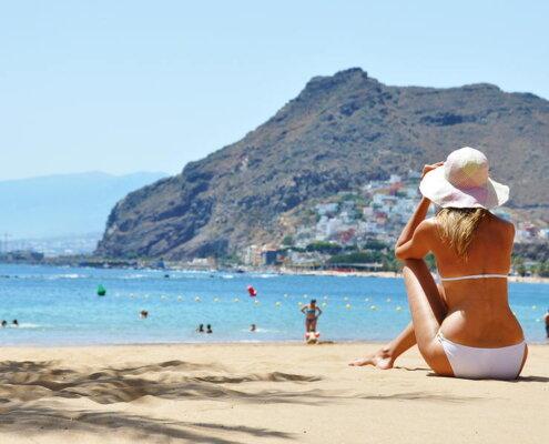 chica sentada en la playa mirando el mar y la montaña