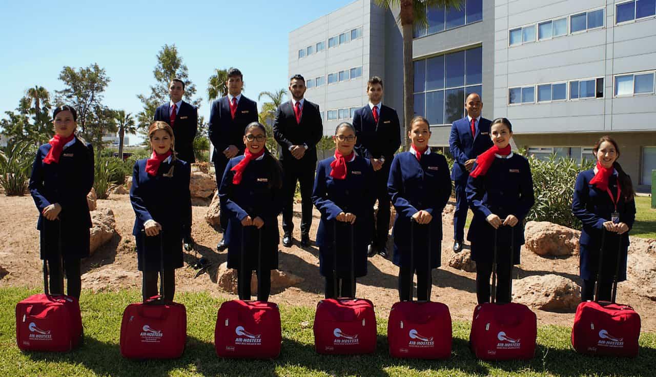 grupo de estudiantes de air hostess malaga parados sobre cesped uniformados y con maleta