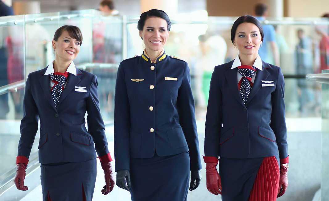 tres azafatas en aeropuerto caminando sonrientes