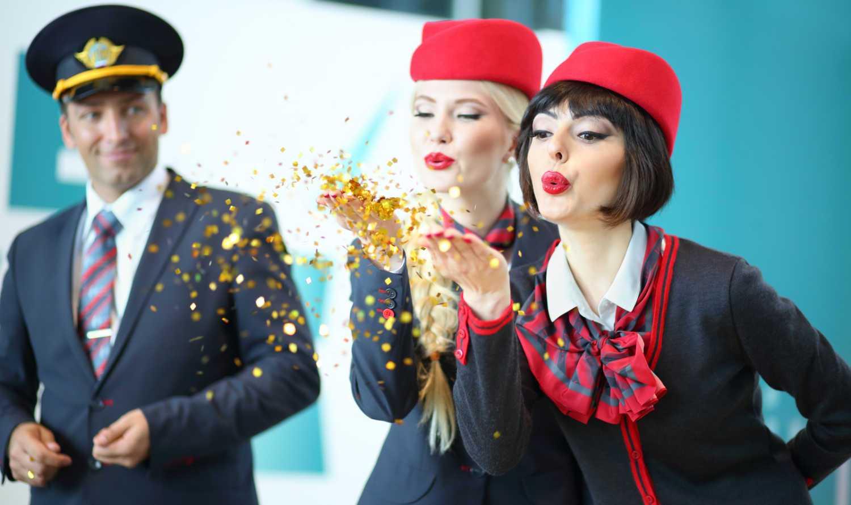 azafatas con gorro rojo soplando confeti