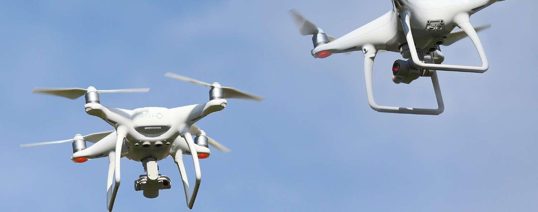 dos drones dji phantom en vuelo con fondo azul claro