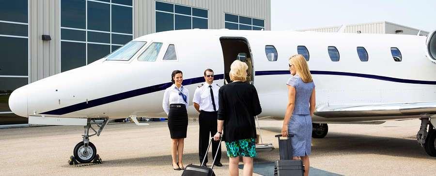 piloto y azafata recibiendo a pasajeros de avion privado