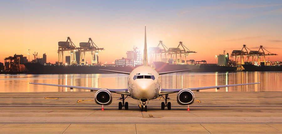 avion de pasajeros en pista con fondo de gruas iluminadas al atardeces