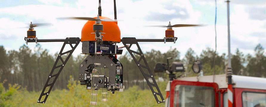 dron para extincion de incendios en vuelo con fondo de arboles y camion de bomberos
