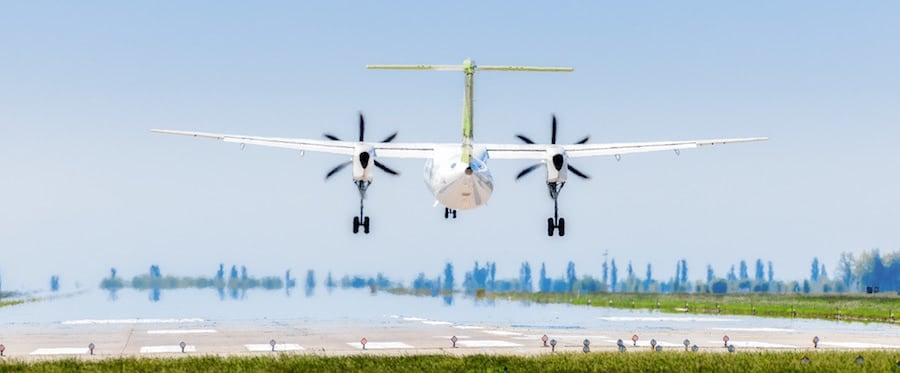 vista trasera de avion aterrizando en pista con fondo azul y arboles