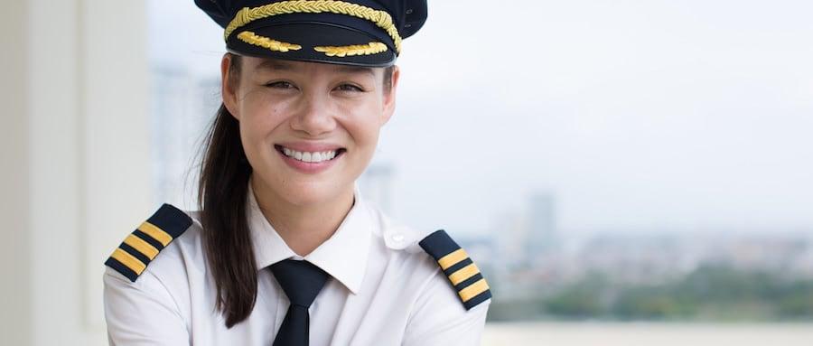 retrato de mujer piloto sonriente con uniforme, corbata, galones y gorra de piloto