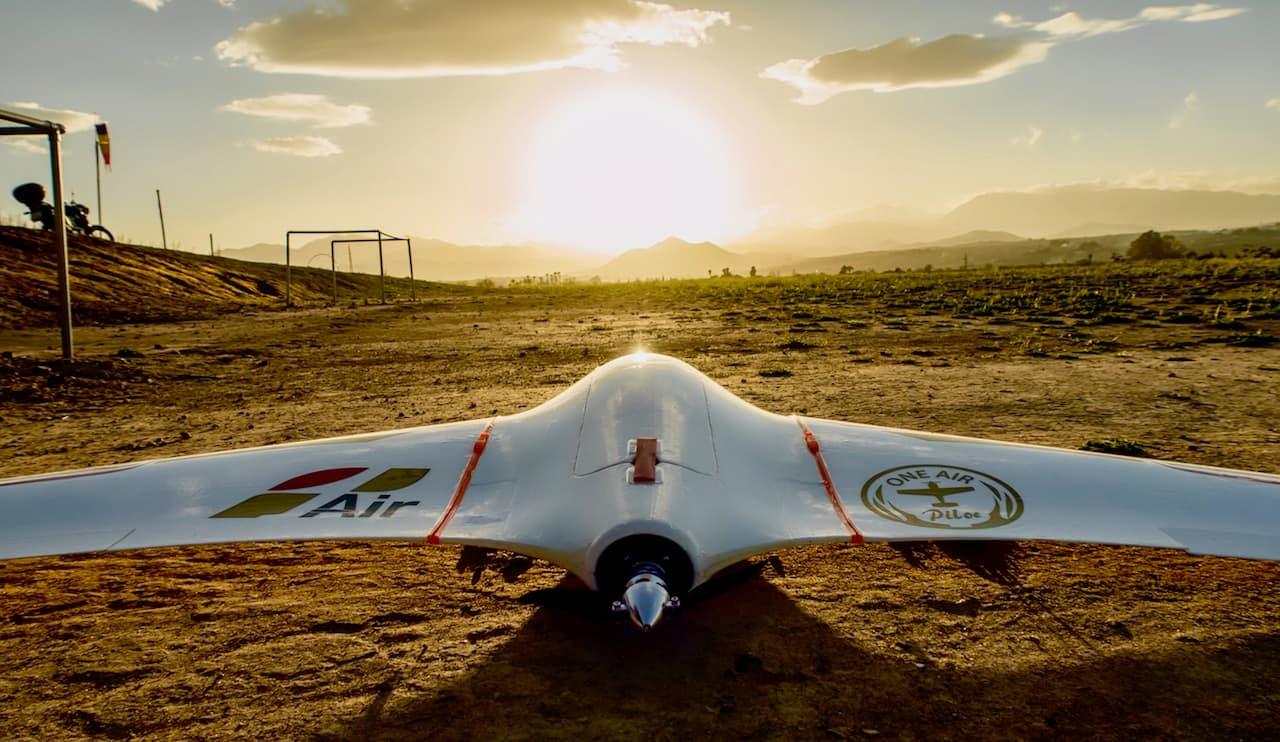 drone de ala fija aterrizado en el suelo con una puesta de sol al fondo al amanecer