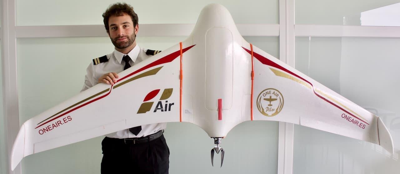 drone de ala fija y un piloto sujetandola en alto