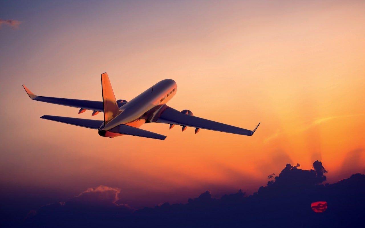 vista de la parte de atras de un avion despegando con nubes abajo y un cielo despejado al atardecer de color naranja