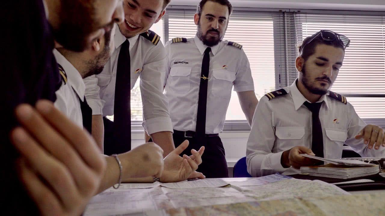 instructor de vuelo en clase de formacion de pilotos de avion con cuatro alumnos