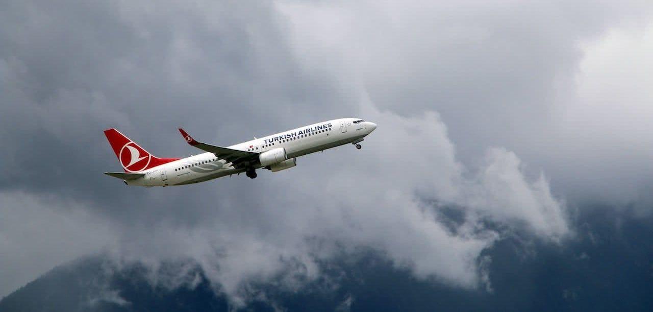 avion de la aerolinea turkish airlines sobrevolando una montaña rodeada de nubes