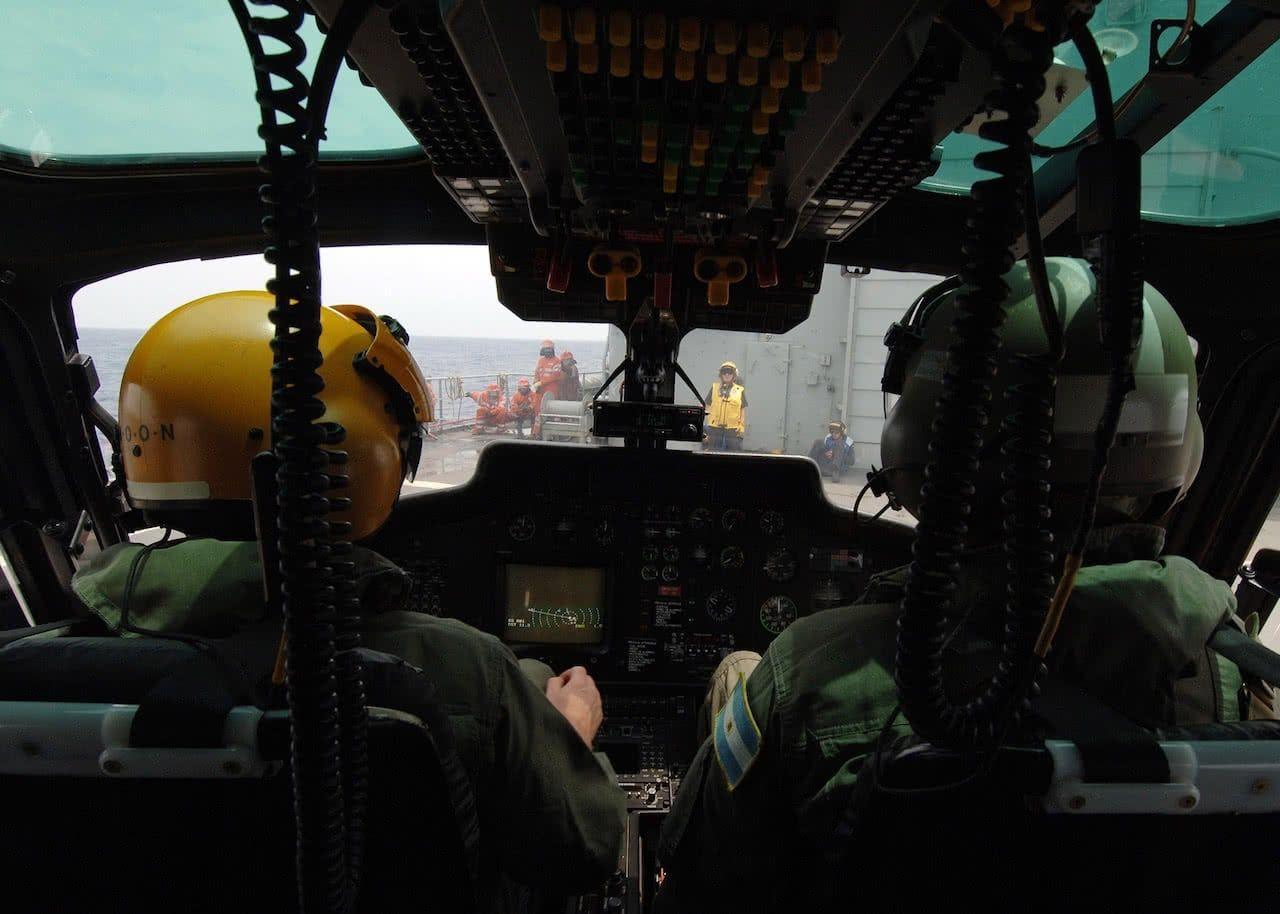 Dos pilotos dentro de la cabina de un helicoptero del ejercito