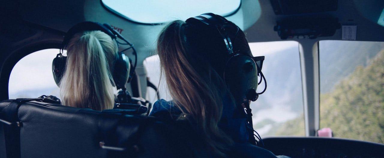 dos chicas piloto con sus cascos de comunicacion puestos en la cabina de un avión