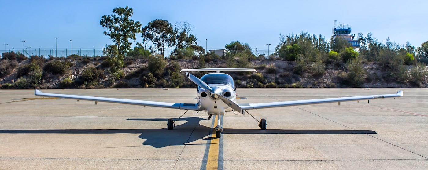 avioneta plateada en pista con fonde de vegetacion