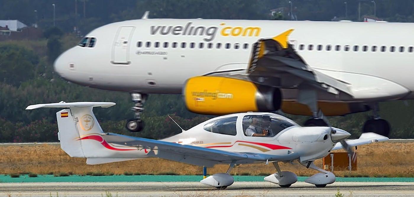 avion diamond da 42 de la escuela de aviación one air en la pista de despegue cruzandose con un avión comercial de la aerolinea Monarch
