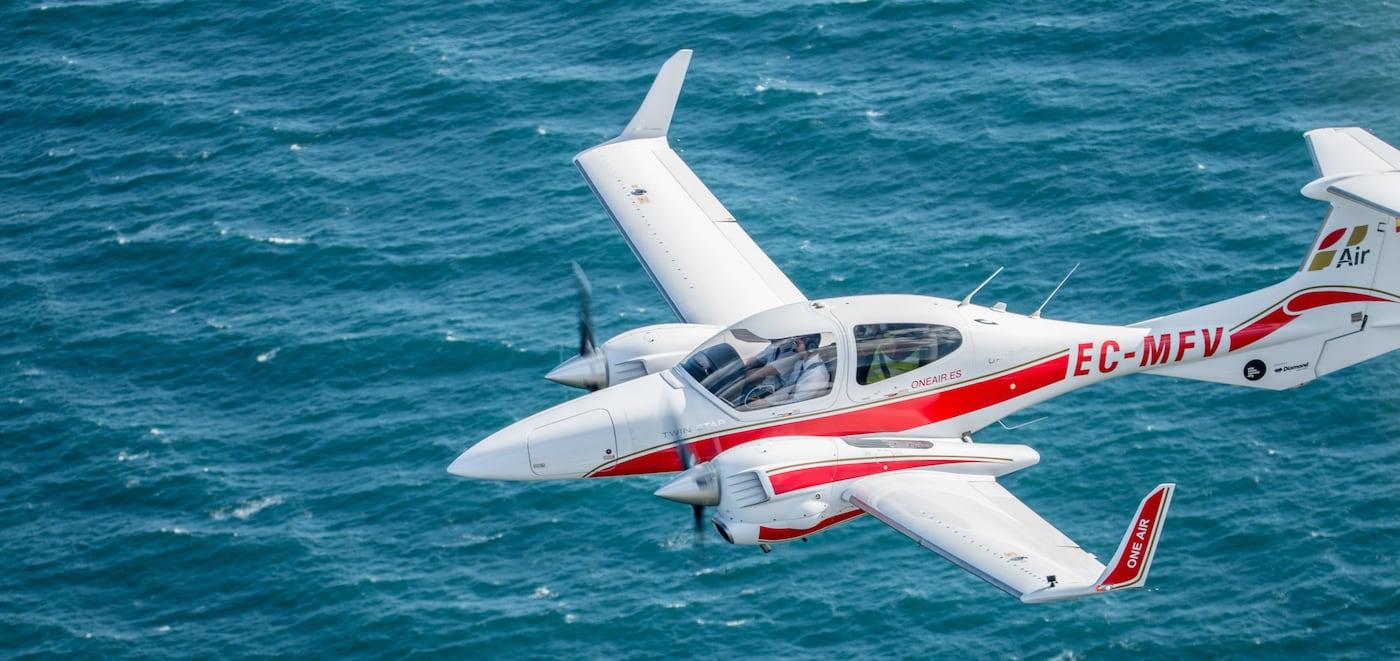 avion bimotor de la escuela de aviacion one air sobrevolando el mar
