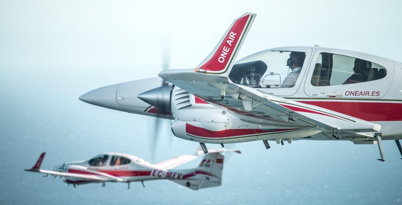 dos aviones diamond da42 de la escuela de aviacion one air volando juntos por encima del mar