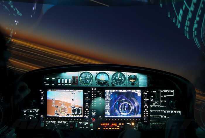 panel de mandos de la cabina de un avion diamond da20 con pantallas del garmin 1000 mientras vuela de noche