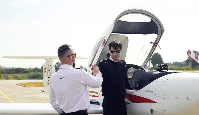 piloto e instructor de vuelo estrechando las manos despues de aterrizar el avion diamond da20