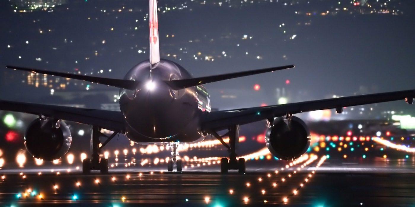 trasera de avion de pasajeros avansando en pista de despegue de noche