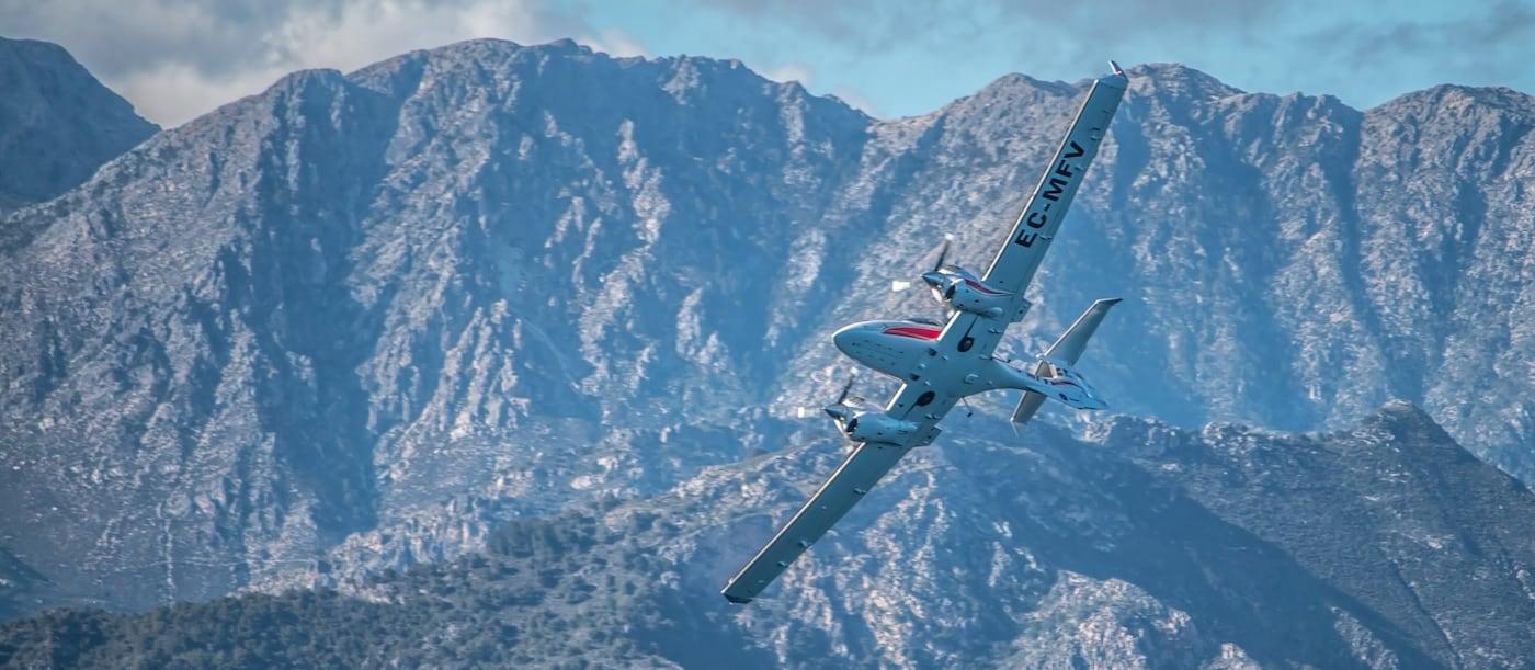 vista desde abajo de aeronave diamond da42 de one air aviacion volando con montanas de fondo