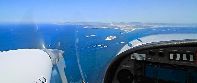 helice y mandos de avion con paisaje de islas desde el aire