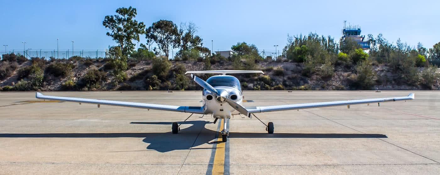 aeronave plateada en pista con fonde de vegetacion