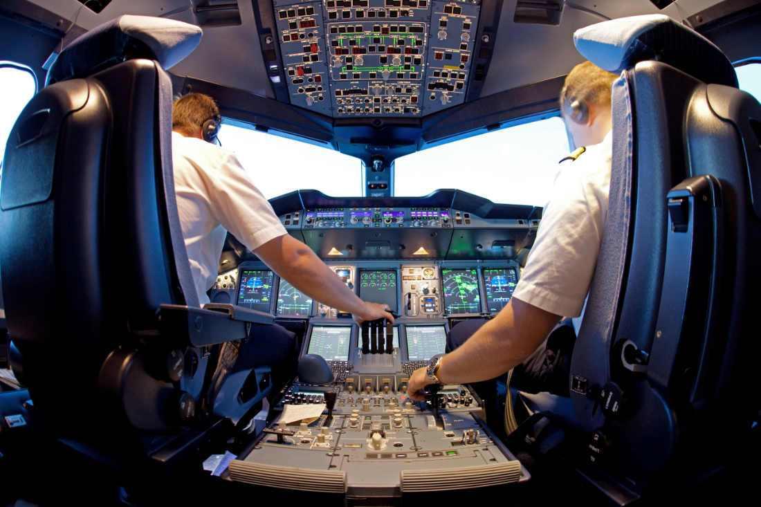 vista desde atras de pilotos de avion en cabina con cascos