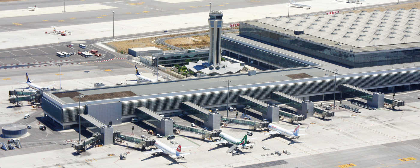 vista aerea de pista de aeropuerto con varios aviones cargando pasajeros y torre de control en el centro