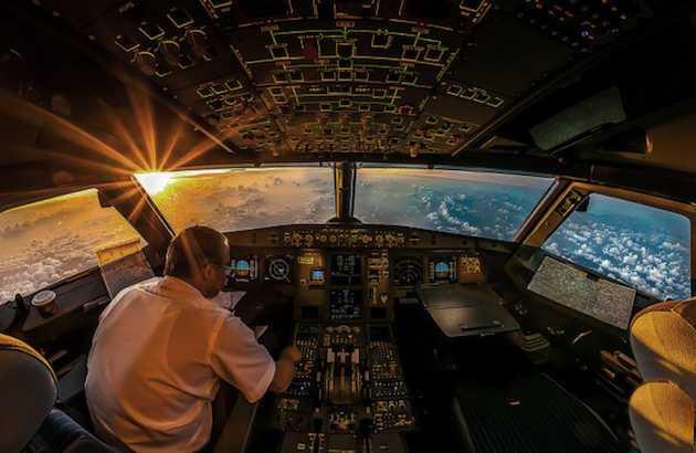 cabina de avion de pasajeros con piloto y paisaje de nubes