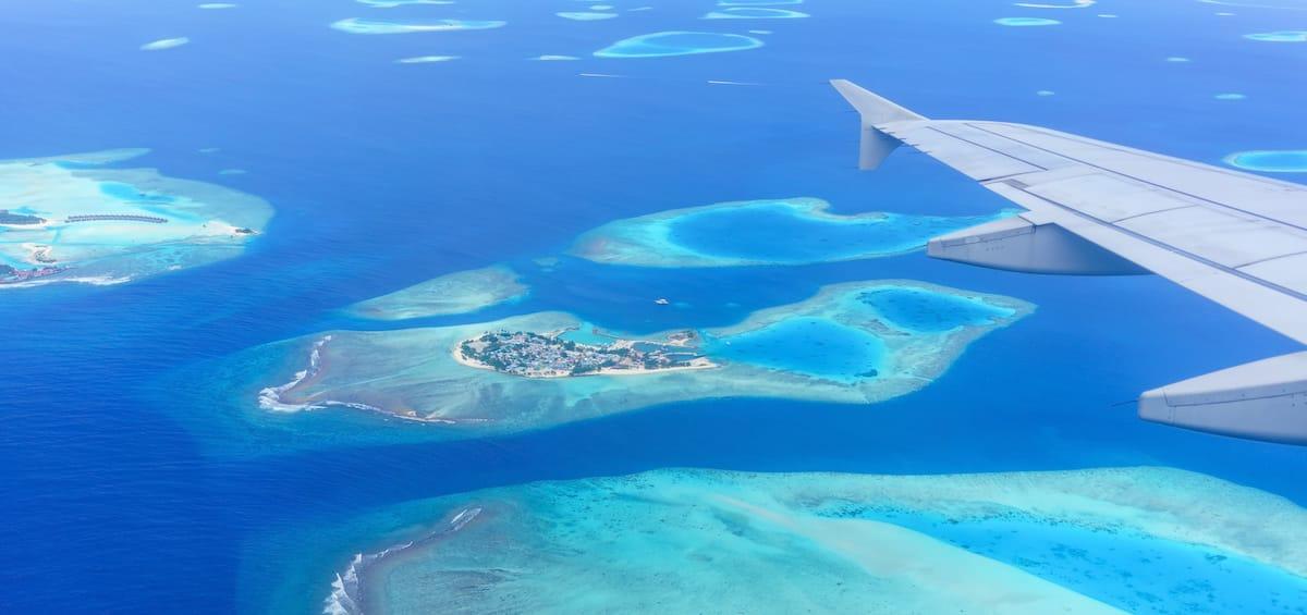 vista aerea de isla en el oceano desde ventanilla de avion con ala y motores a un lado
