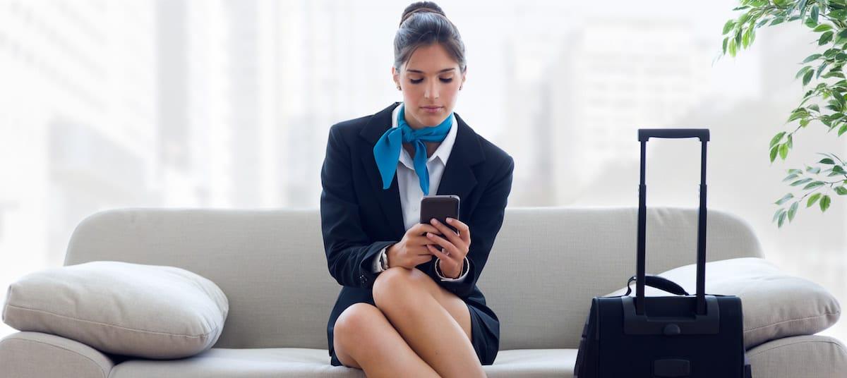 auxiliar de vuelo con smartphone y maleta