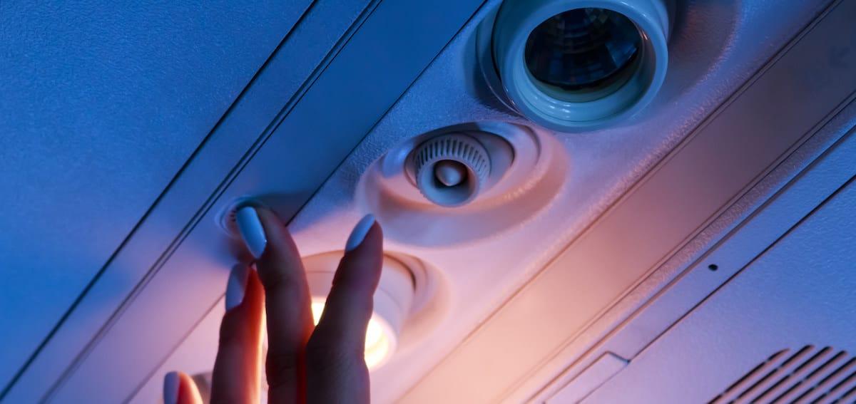 pasajera de vuelo pulsando el boton de llamada al auxiliar de vuelo