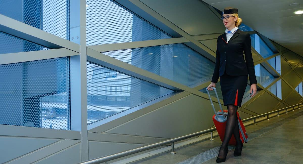 auxiliar de vuelo con uniforme y maleta llegando a aeropuerto despues de un vuelo