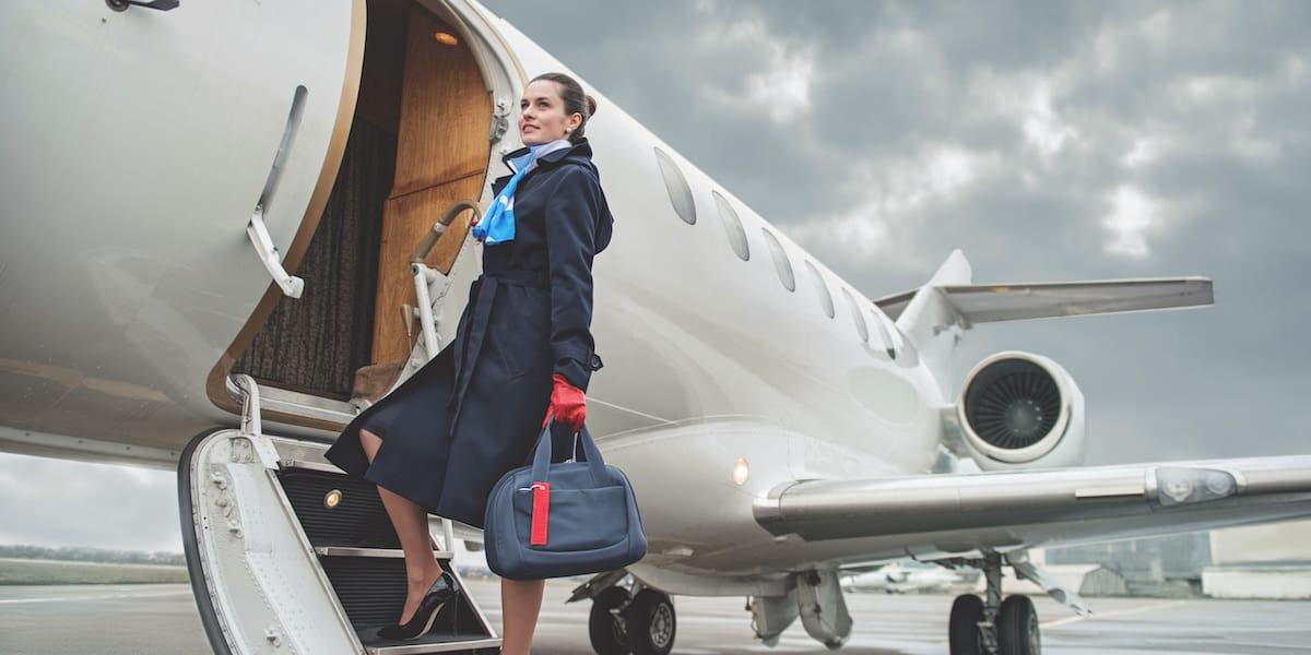 auxiliar de vuelo subiendo a avion con uniforme y maleta de mano