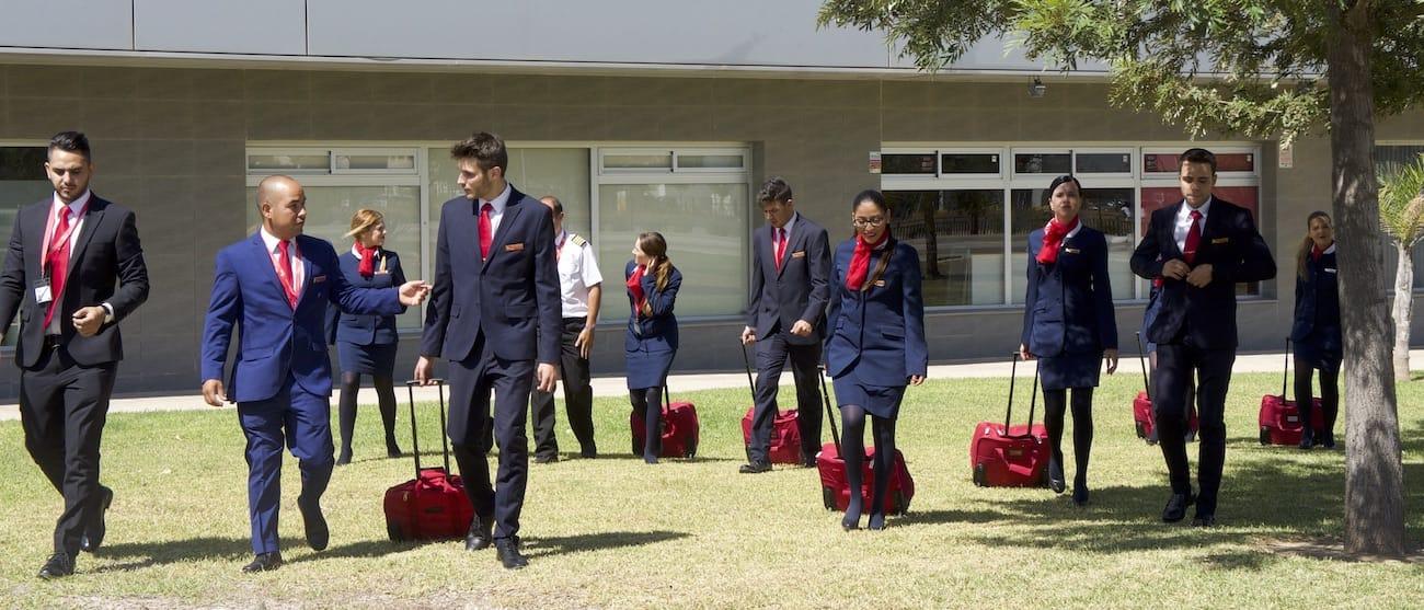 alumnos de air hostess malaga caminando por la hierba con uniforme y maleta