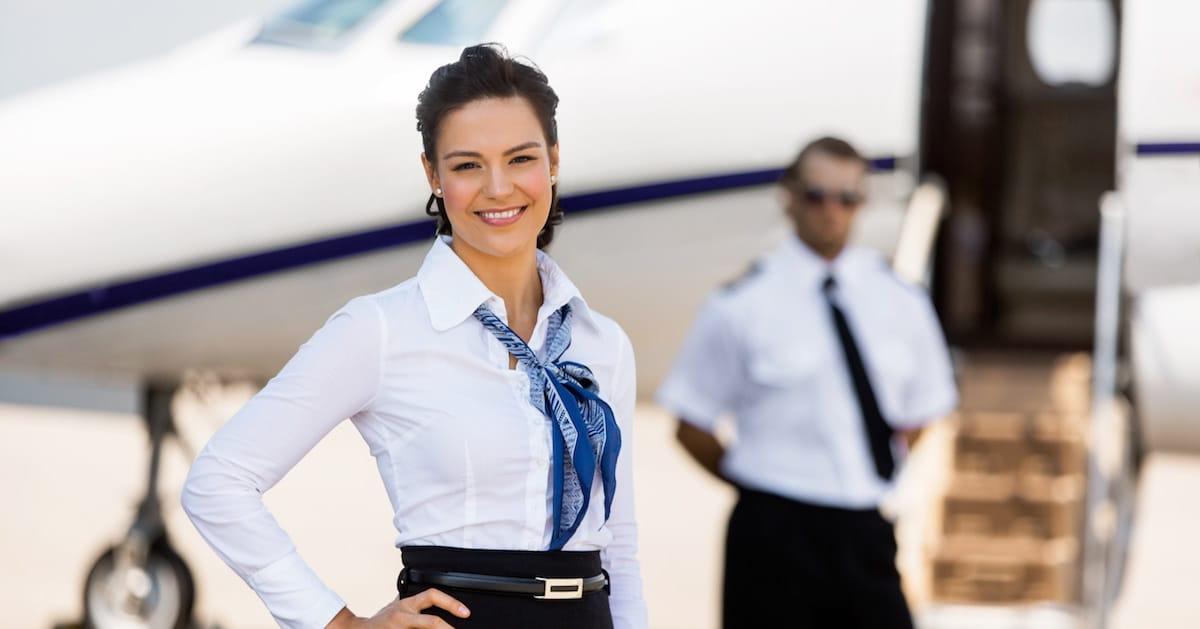 auxiliar de vuelo sonriente frente a avion con piloto en segundo plano