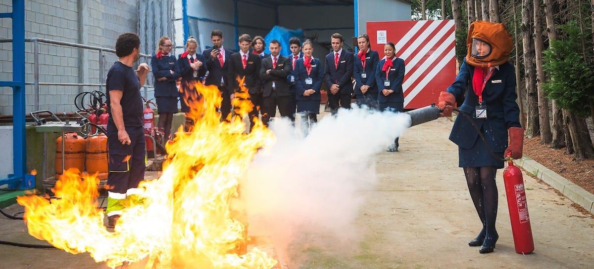 estudiante de tcp de air hostess apagando un fuego durante las practicas de emergencias